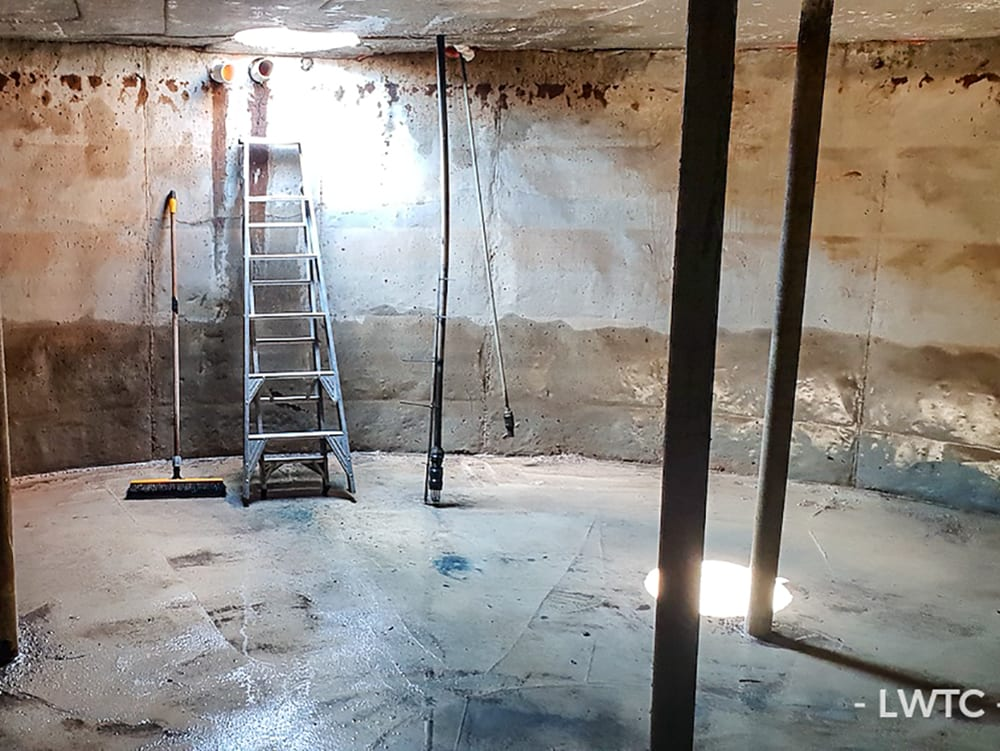 This image shows a concrete water tank that has been cleaned and completely drained.